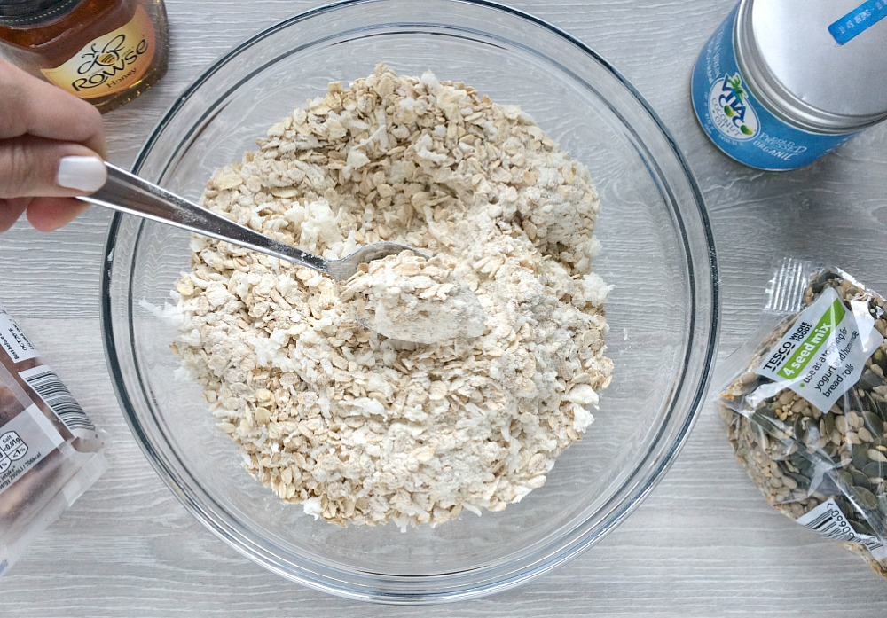 A bowl of oats with a spoon in it, with a seed mix and some honey next to it