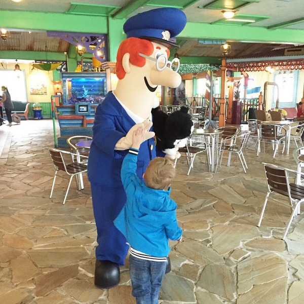 A Postman Pat character high fiving a young boy