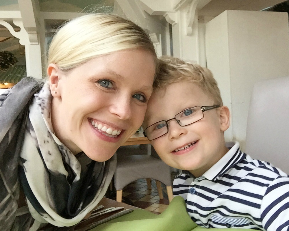 A mother and son smiling in a restaurant
