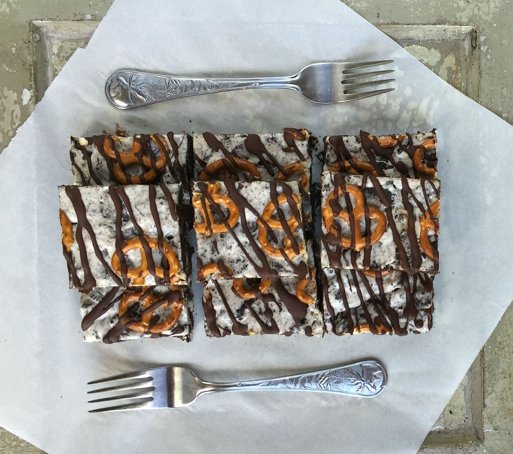 Salted oreo cookie bars stacked on greaseproof paper, with 2 forks