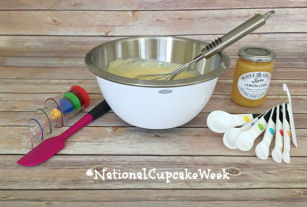 A mixing bowl filled with cake batter and a whisk is stood next to a jar of lemon curd, some measuring spoons and a spatula