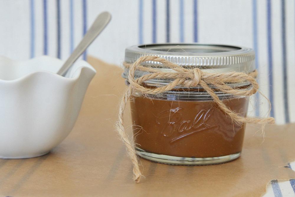 A jar of homemade caramel sauce next to a white bowl.