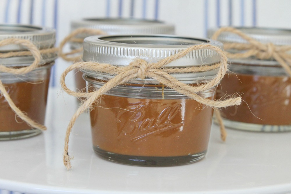 4 jars filled with homemade caramel and tied with string in bows