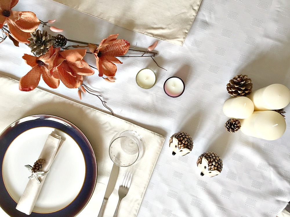 A top down view of a Thanksgiving table setting, with pine cones, candles and hedgehogs