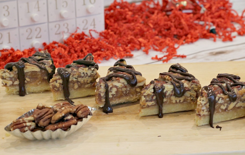 Coconut Caramel Pecan Triangles next to a dish of pecans and with an advent calendar behind