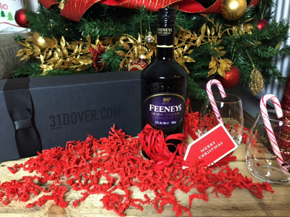 A bottle of 31Dover Feeney's Irish cream next to a Christmas tree and 2 tumblers with candy canes in them