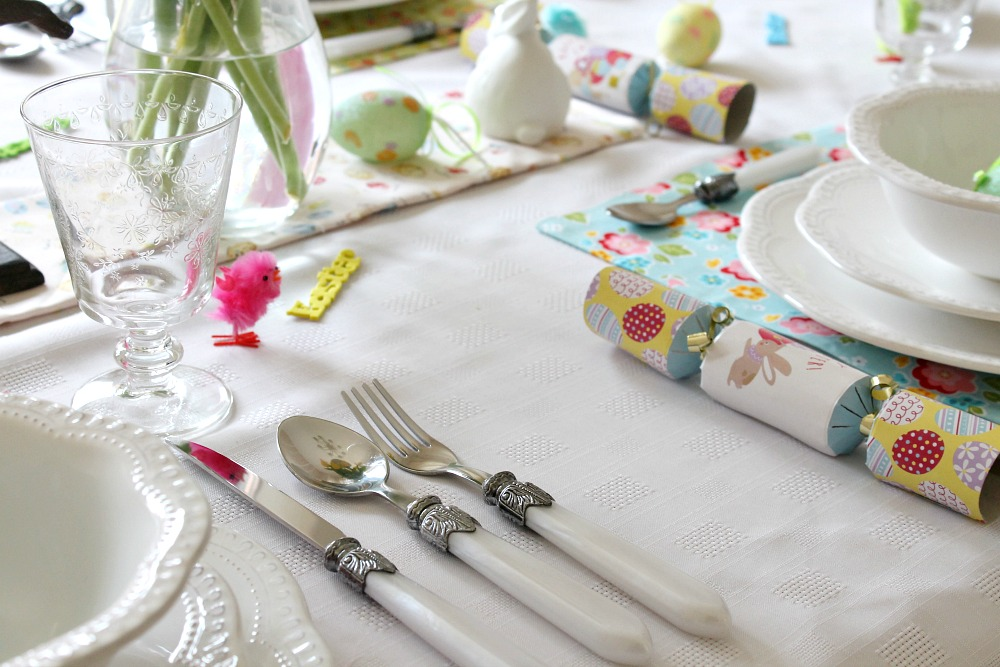 An Easter table set with crackers, decorative eggs and white crockery