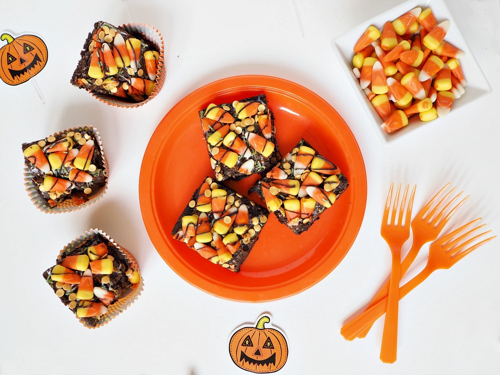 3 Halloween chocolate brownies on an orange plate, with 3 more brownies beside it, a bowl of candy corn and 3 orange forks.