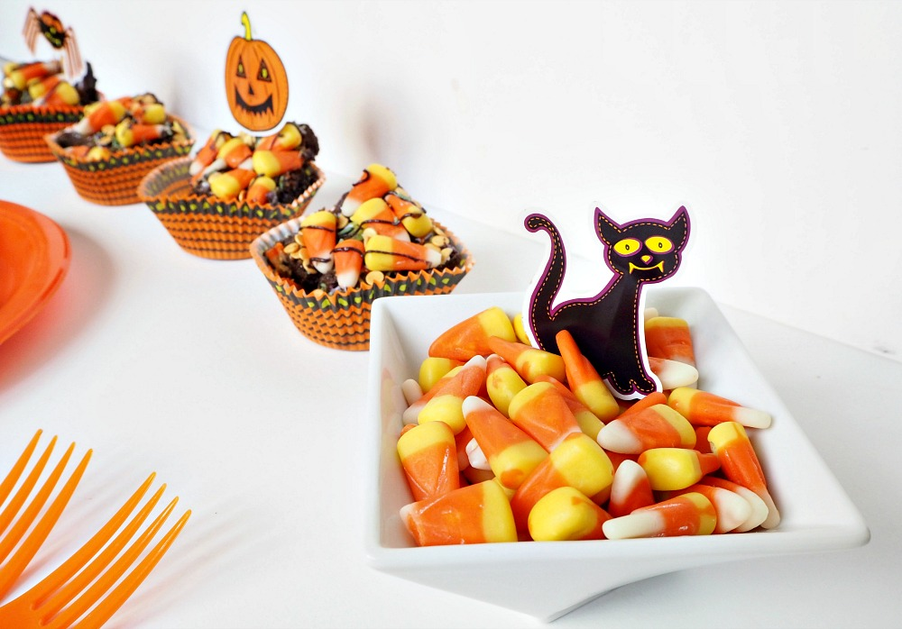 A bowl of candy corn with a black cat figure in it, and cupcake cases with Halloween brownies in them