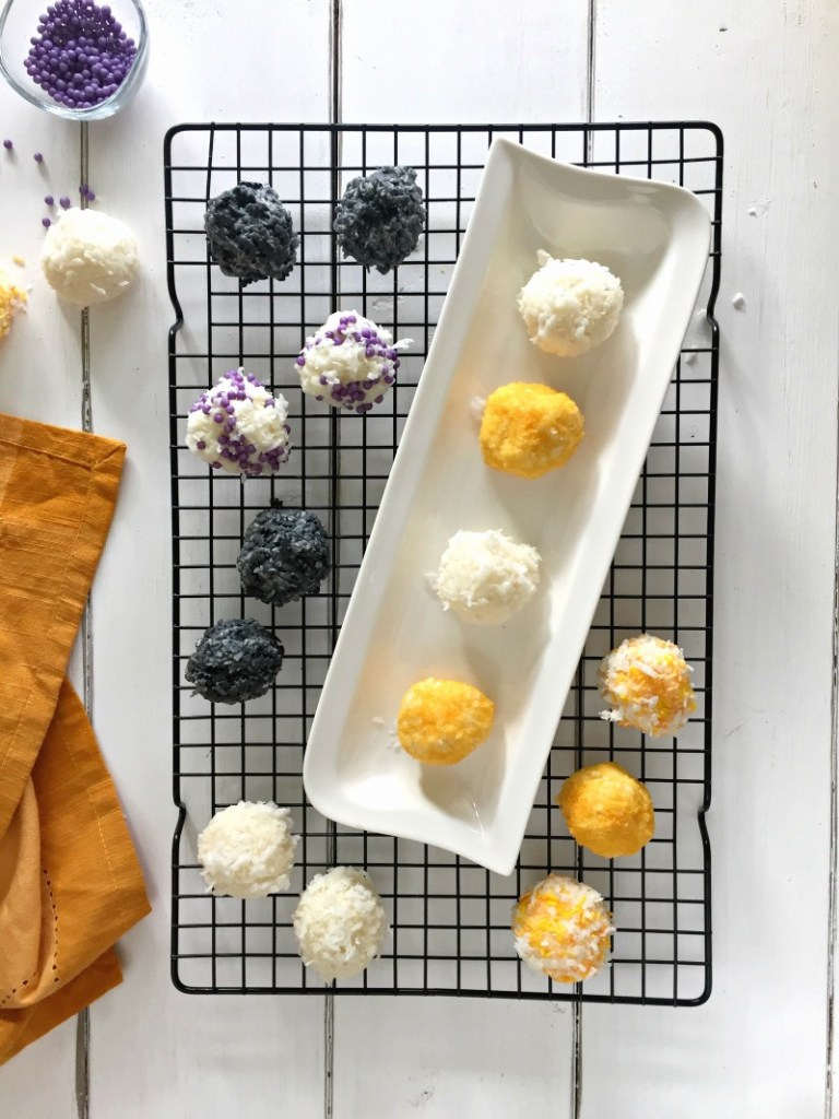 A cooling rack with different coloured coconut Halloween snowballs on it