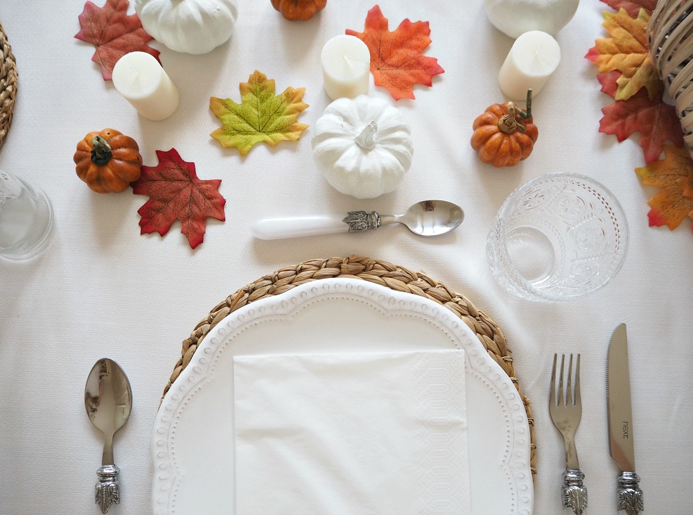 A Thanksgiving table setting with white pumpkins, fake orange pumpkins, fake leaves and candles