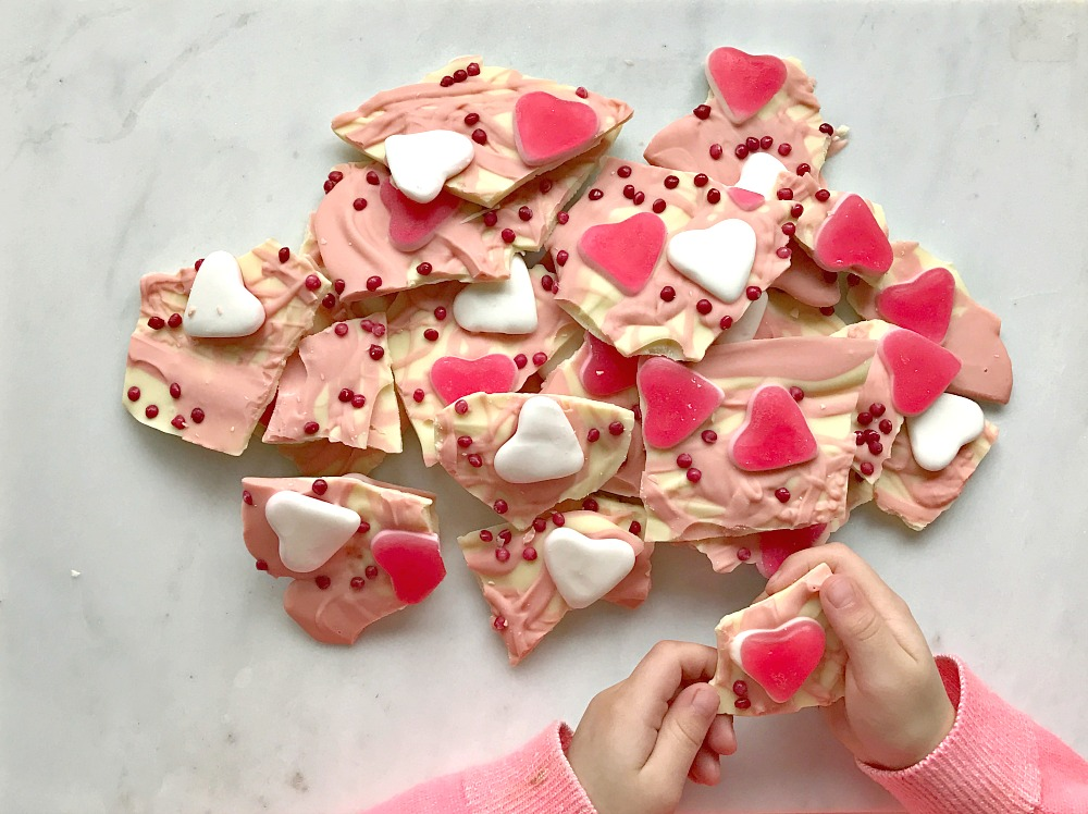 A childs hand holding a piece of chocolate bark with hearts and sprinkles on it for Valentine's Day. There is a big pile of bark next to her.