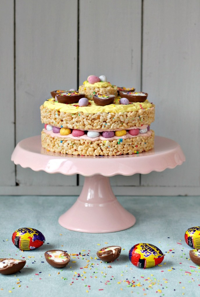 An Easter cake make out of rice crispy treats sits on a pink cake stand and is surrounded by creme eggs