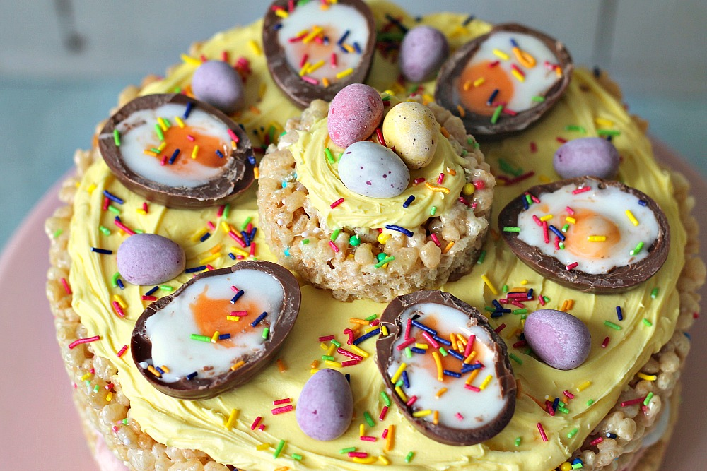An Easter cake make out of rice crispy treats sits on a pink cake stand and topped with yellow icing, creme eggs and mini eggs