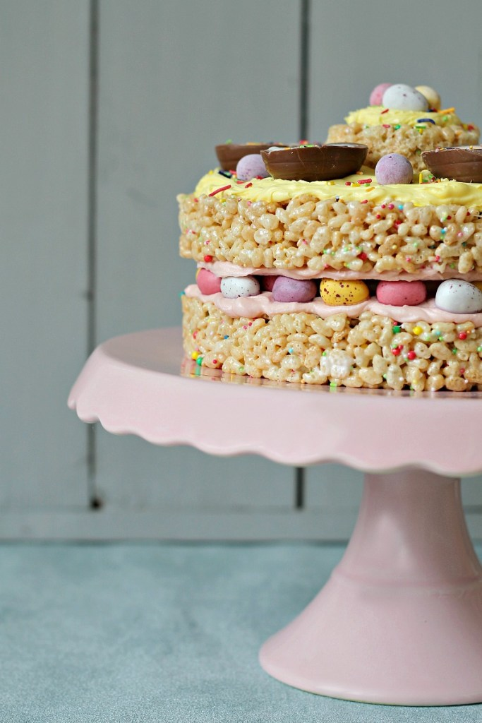 An Easter cake make out of rice crispy treats sits on a pink cake stand