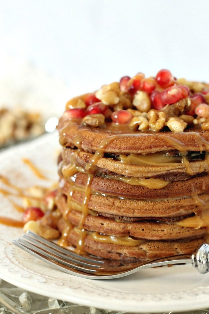 A stacks of cake batter pancakes, with a caramel sauce and topped with pomegranates and walnuts