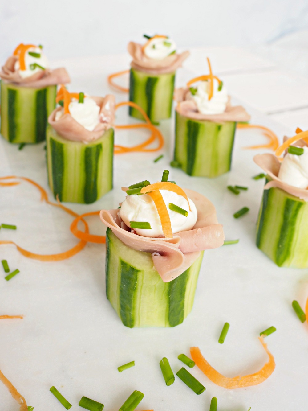 Some kids party food. Ham and cucumber bites, stuffed with cream cheese and topped with shredded carrot and chives