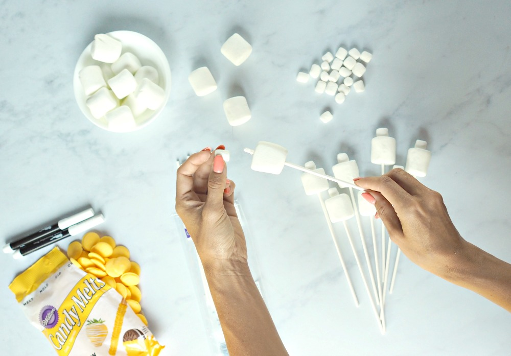 The hands of a woman making lego marshmallow pops, with the ingredients below