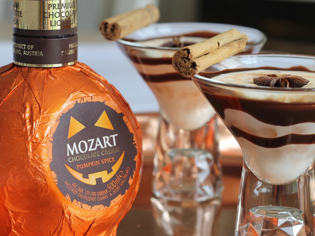 A bottle of chocolate cream pumpkin spice liqueur next to 2 chocolate pumpkin spice martini cocktails with a star anise and a cinnamon stick on top.
