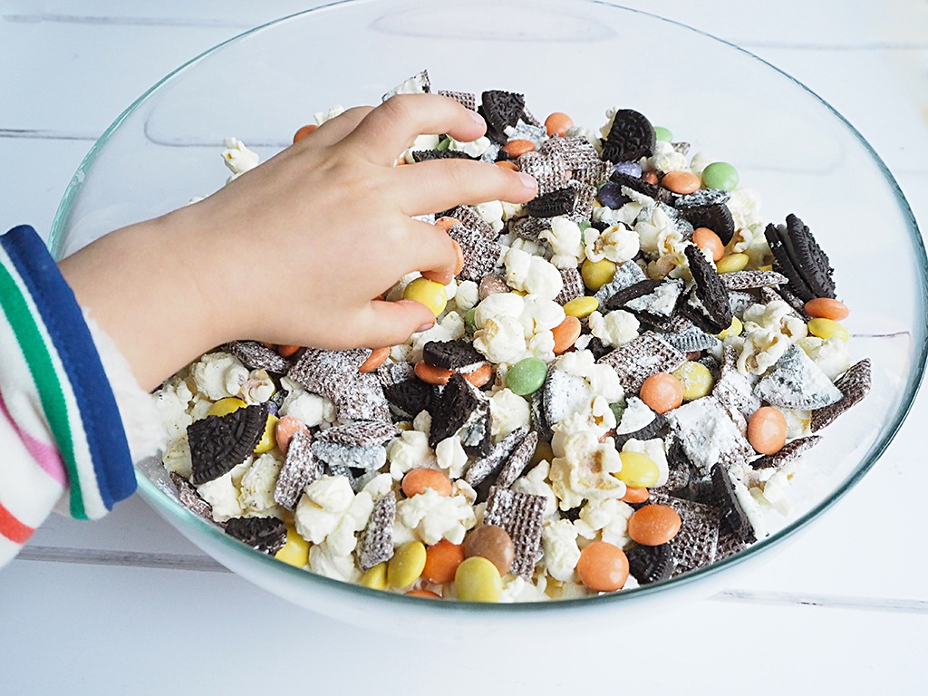 A child's hand reaching in to a bowl of Halloween snack mix