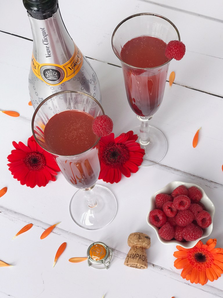 2 Champagne flutes filled with a red cocktail, standing next to a bottle of champagne and a bowl of raspberries