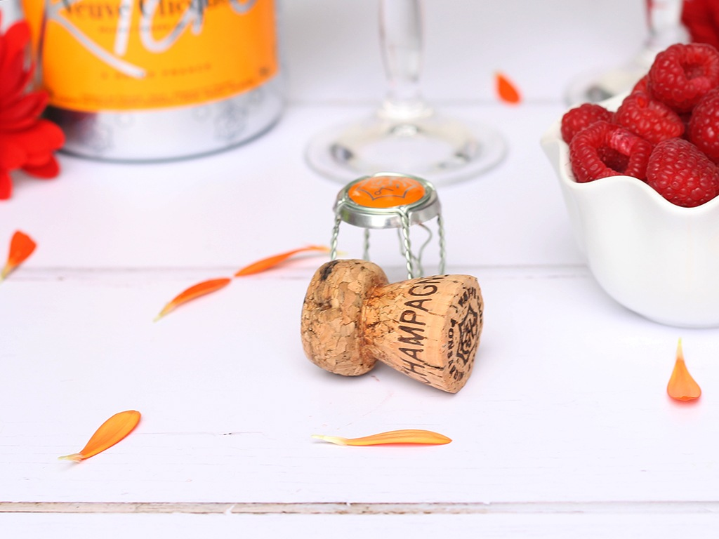 A champagne cork next to a bowl of raspberries
