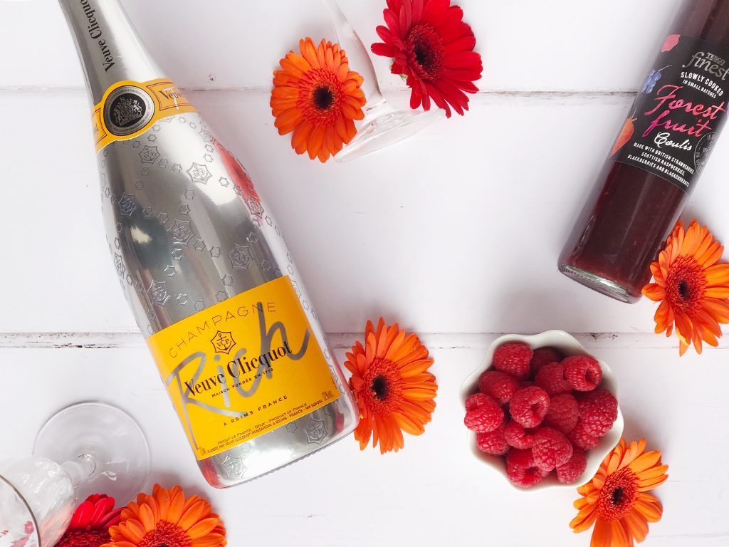 A bottle of Rich Veuve Clicquot  next to a bowl of raspberries and a bottle of forest fruit coulis, surrounded by orange flowers