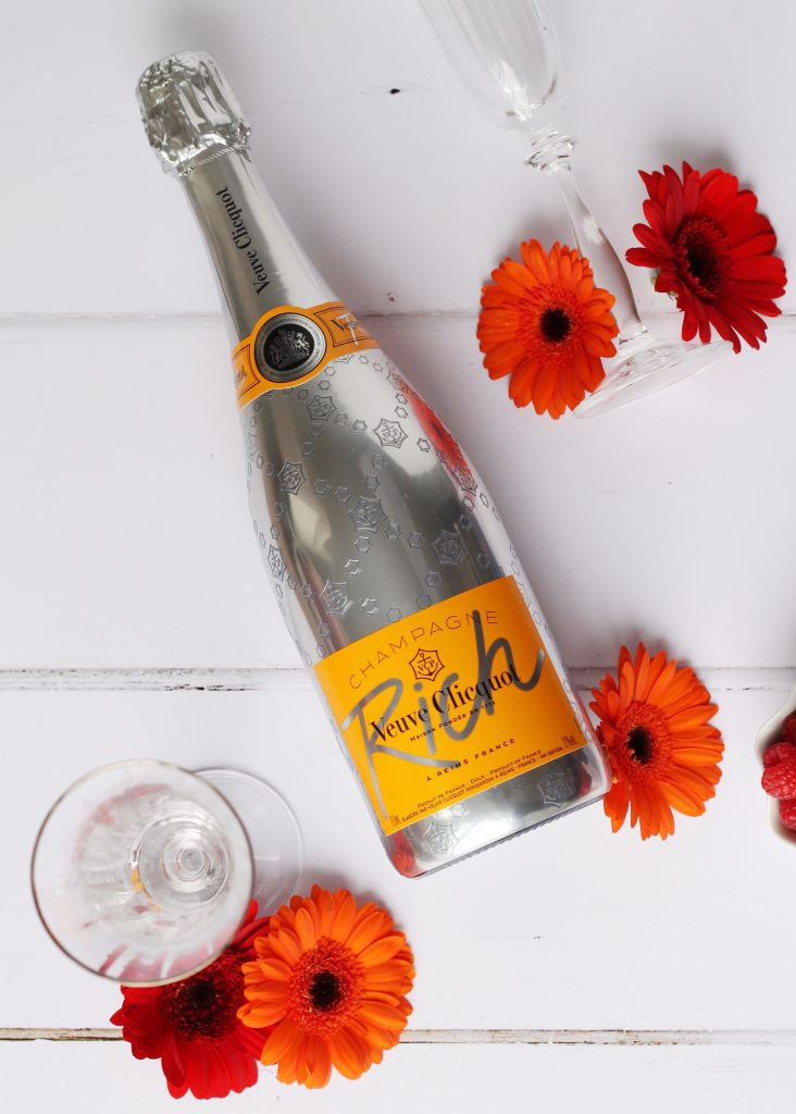 A bottle of Rich Veuve Clicquot lying next to 2 champagne flutes and some red and orange flowers