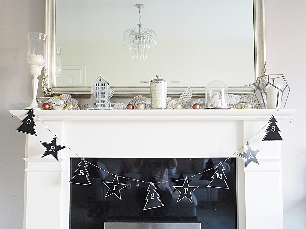 A fireplace mantle decorated for Christmas with candles, a black garland and silver and rose gold accent baubles