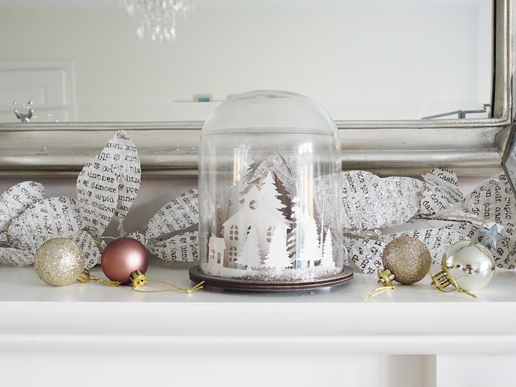 A Christmas snow globe surrounded by rose gold Christmas baubles