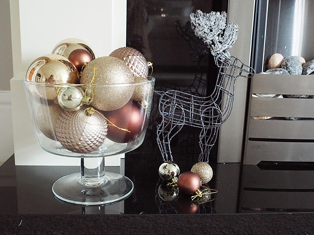 A bowl full of baubles and a silver wire reindeer
