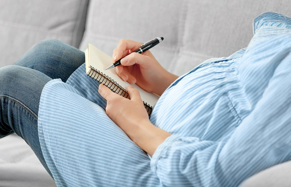 a pregnant women in maternity clothes lying on a sofa with a notebook and pen