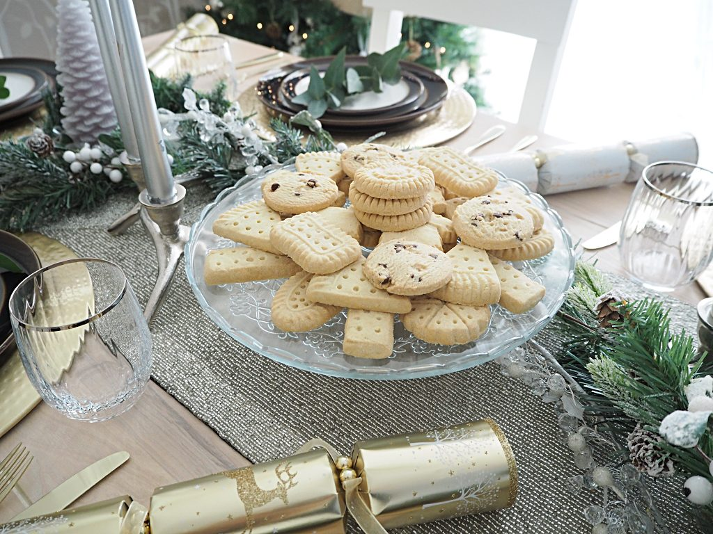 A plate of cookies in the middle of a table set for Christmas diner