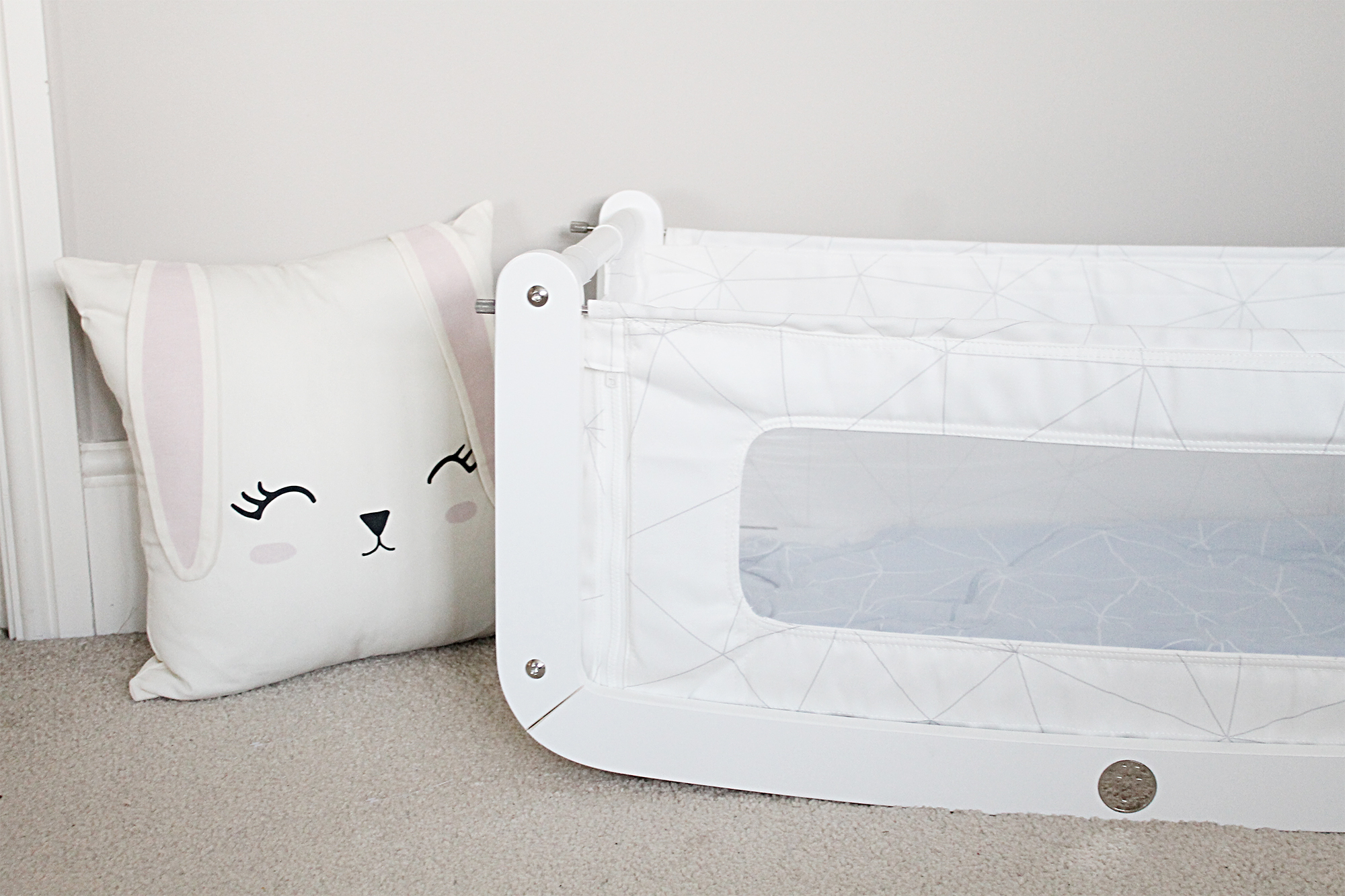 White SnuzPod baby bed on the floor next to a white pillow designed to look like a rabbits head