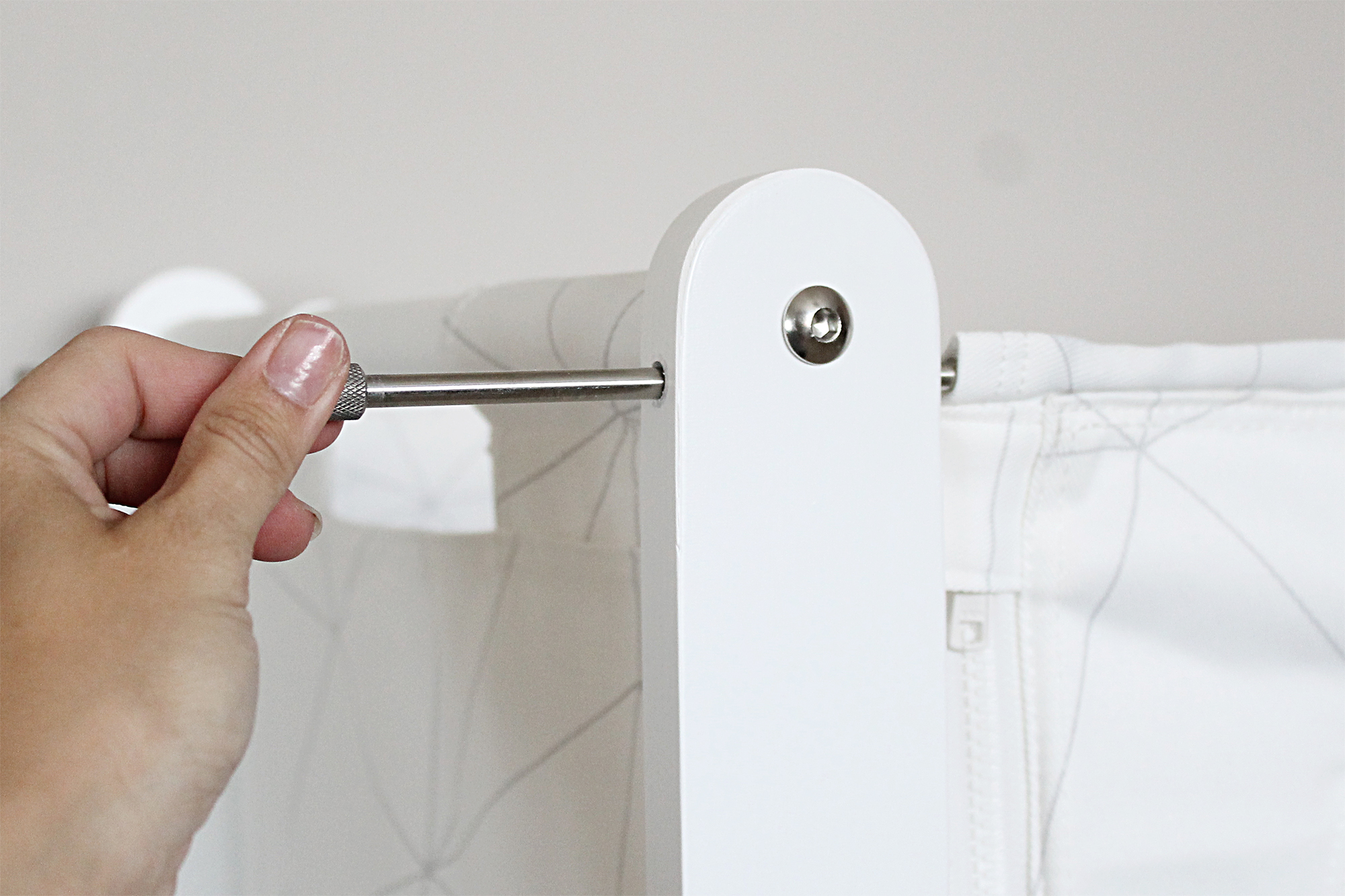 A hand pulling out the pin holding the side of a SnuzPod