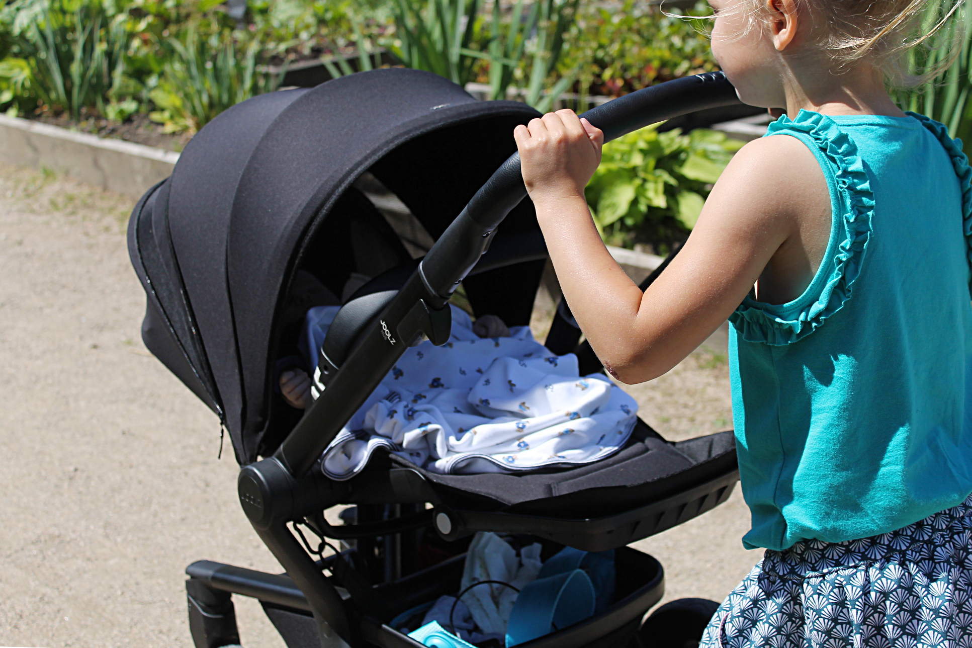 A young girl pushing a baby in a black pram in the park. The focus is on the baby in the pushchair