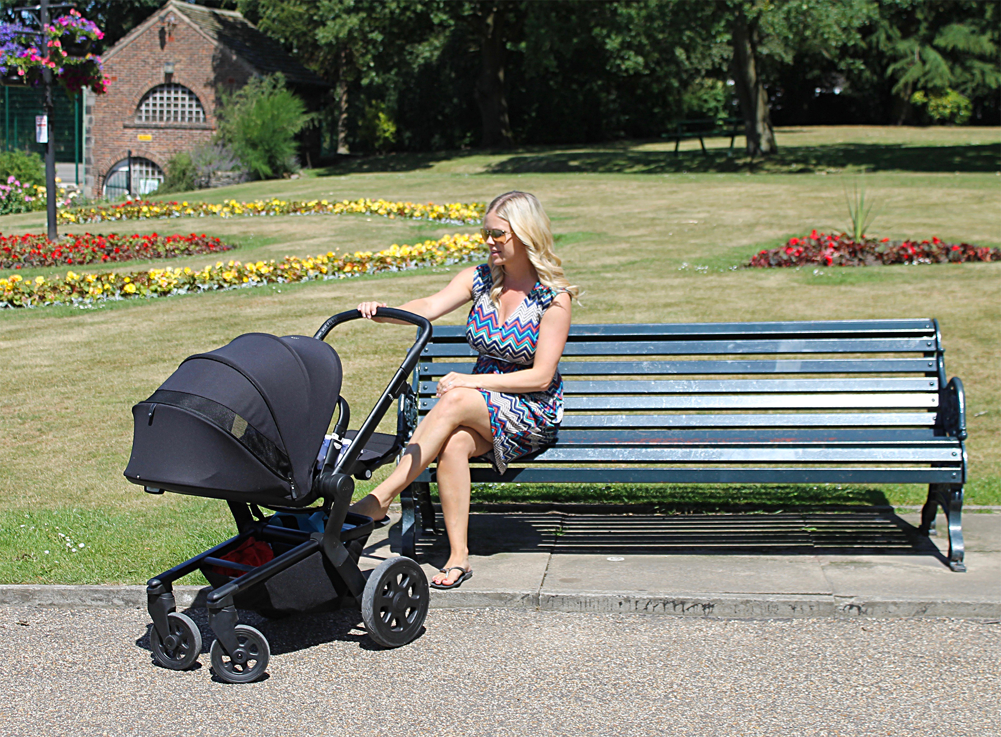 A woman is sitting on a green bench in a park. She is wearing a patterned dress and sunglasses and has her hand on a Joolz hub pushchair