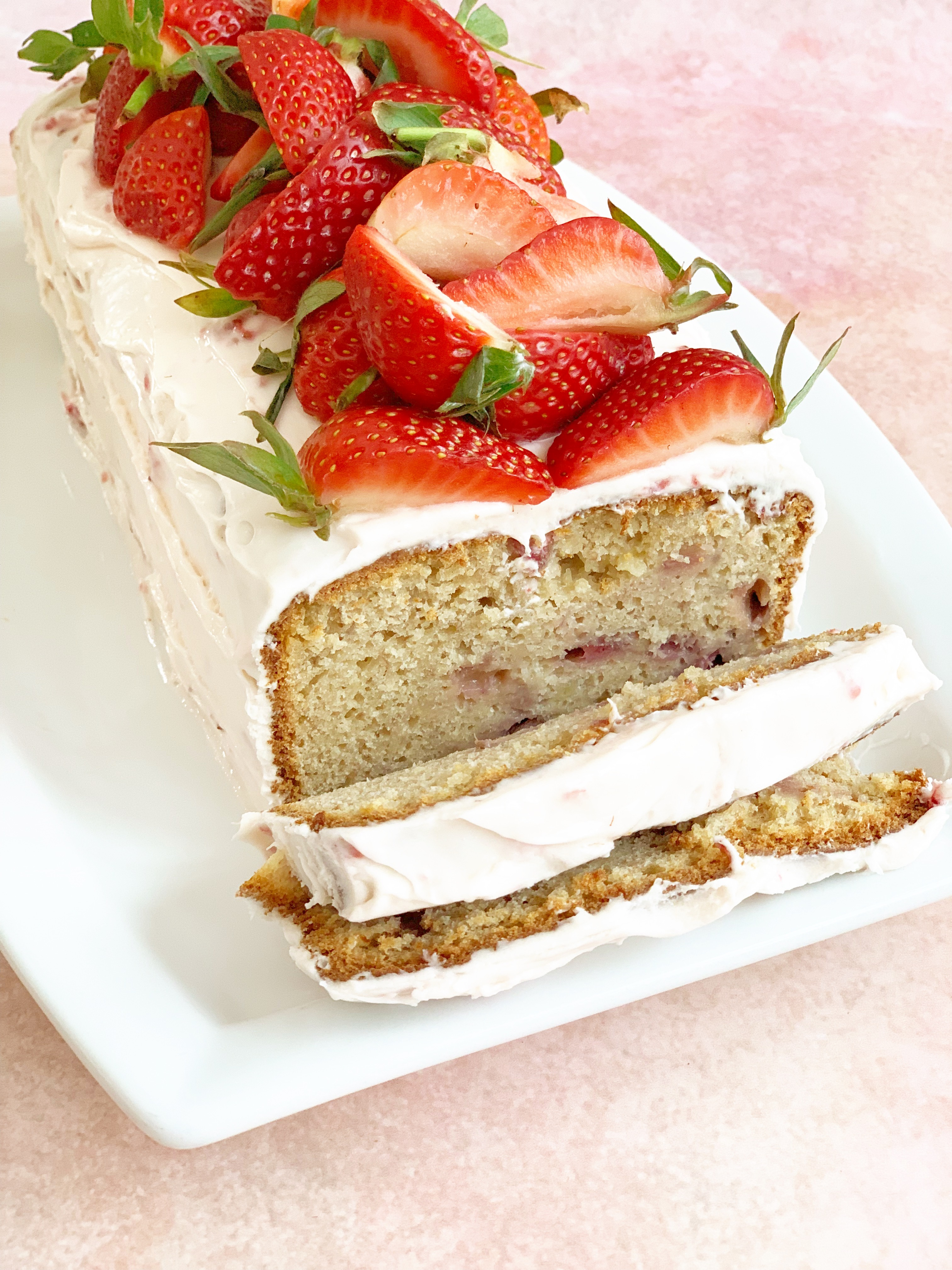 Strawberry bread with cream cheese frosting and fresh strawberries on top. 2 slices have been made in the end to show the internals of the bread
