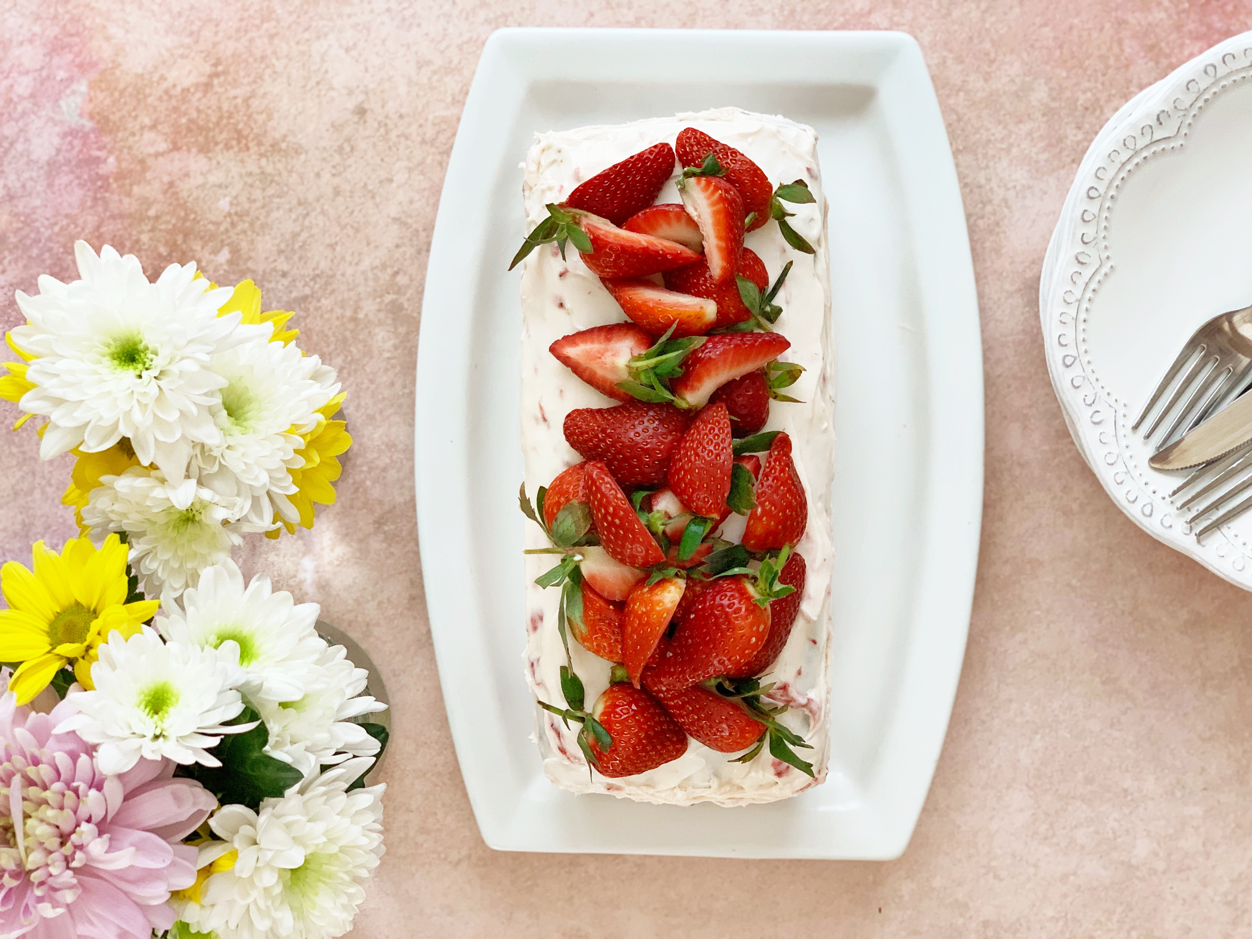 Strawberry bread with cream cheese frosting and fresh strawberries on top. To the left of it is a bunch of flowers in spring colours