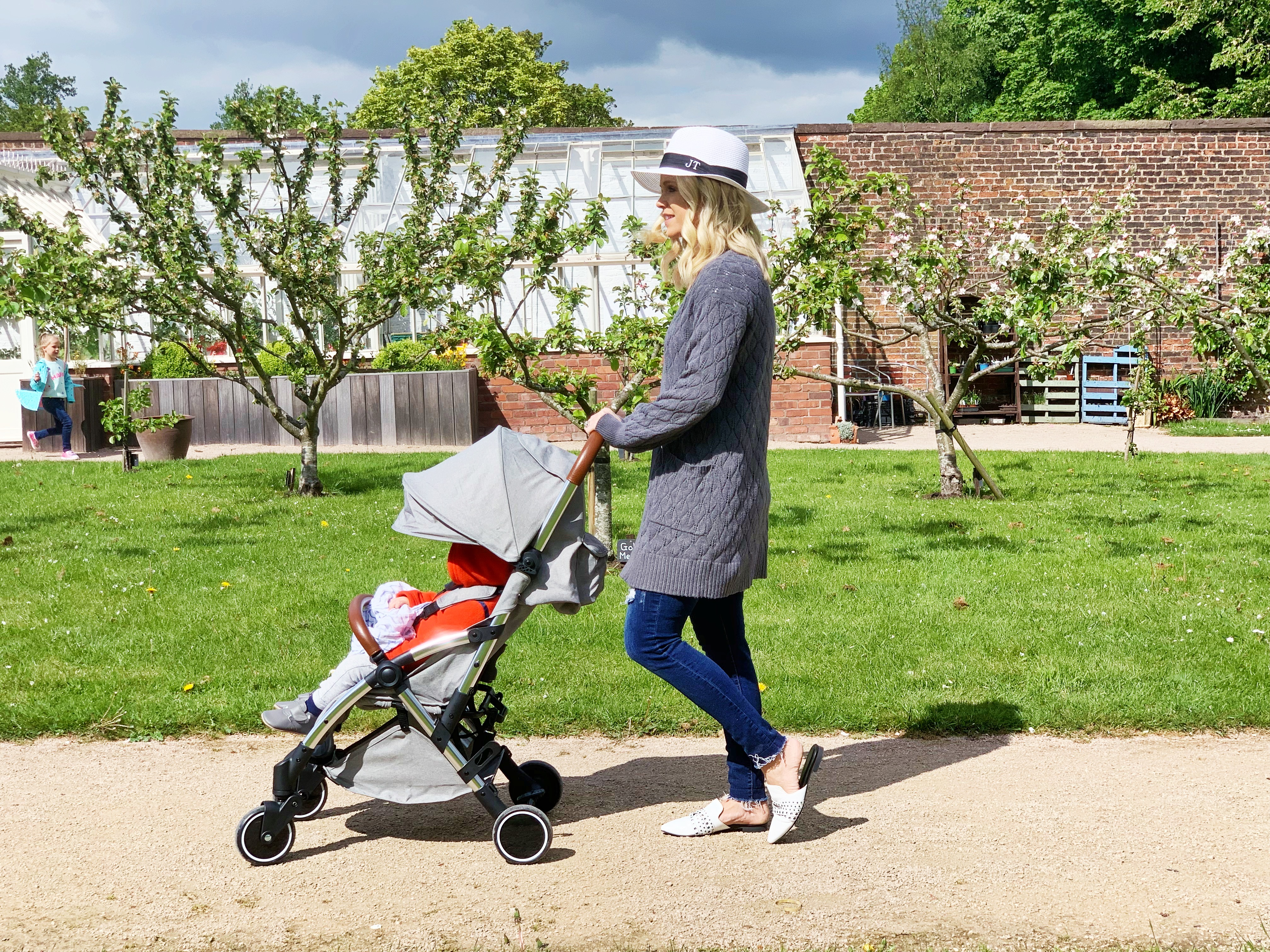 A mother pushing a grey travel stroller in the park. She is wearing a grey cardigan, jeans and a white hat.