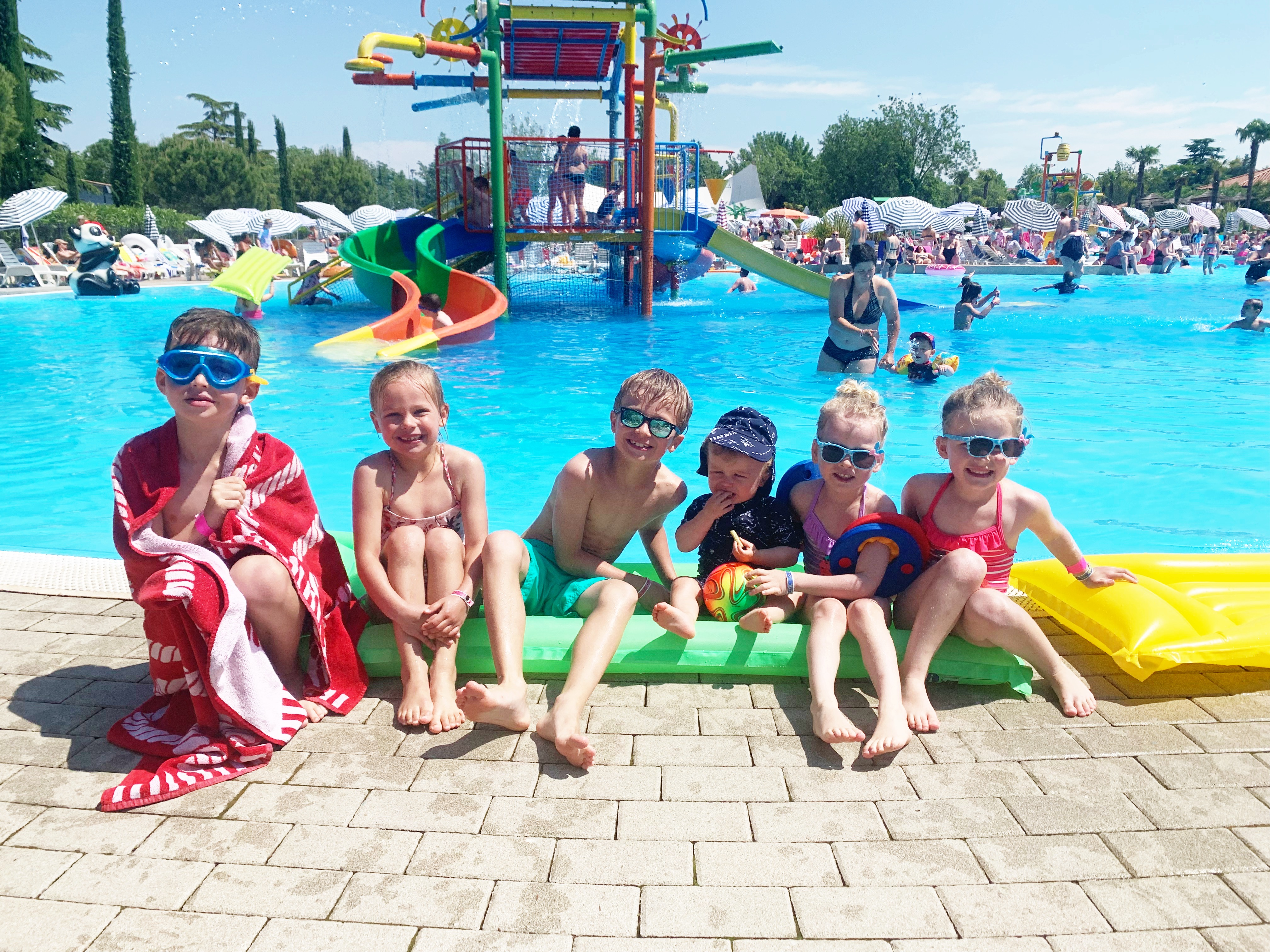 A group of children sit on the edge of a pool in Bella Italia Eurocamp. The waterslides are in the background