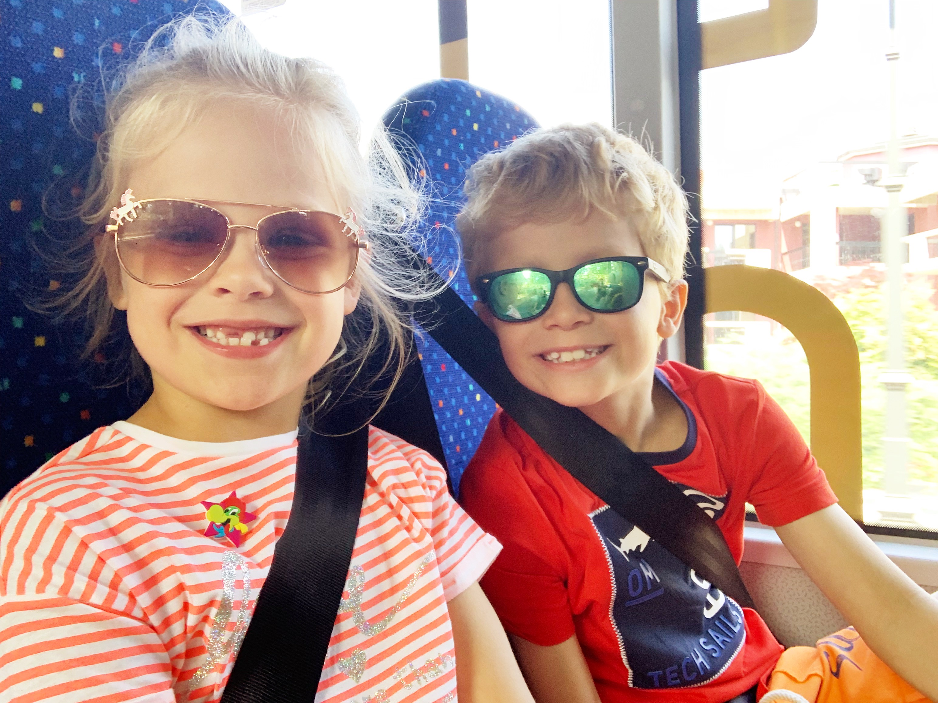 2 children smile for the camera on a bus in Italy