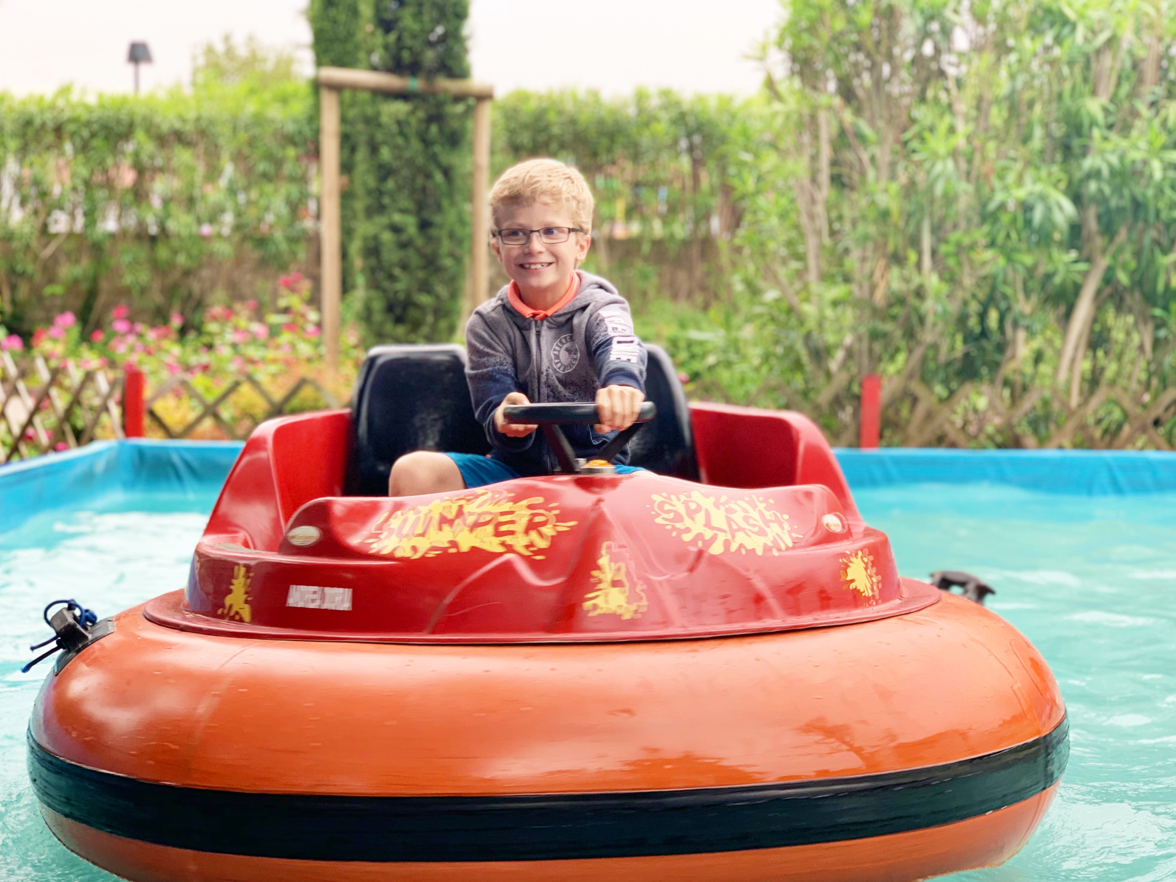 A boy riding a water bumper car in a Eurocamp holiday park