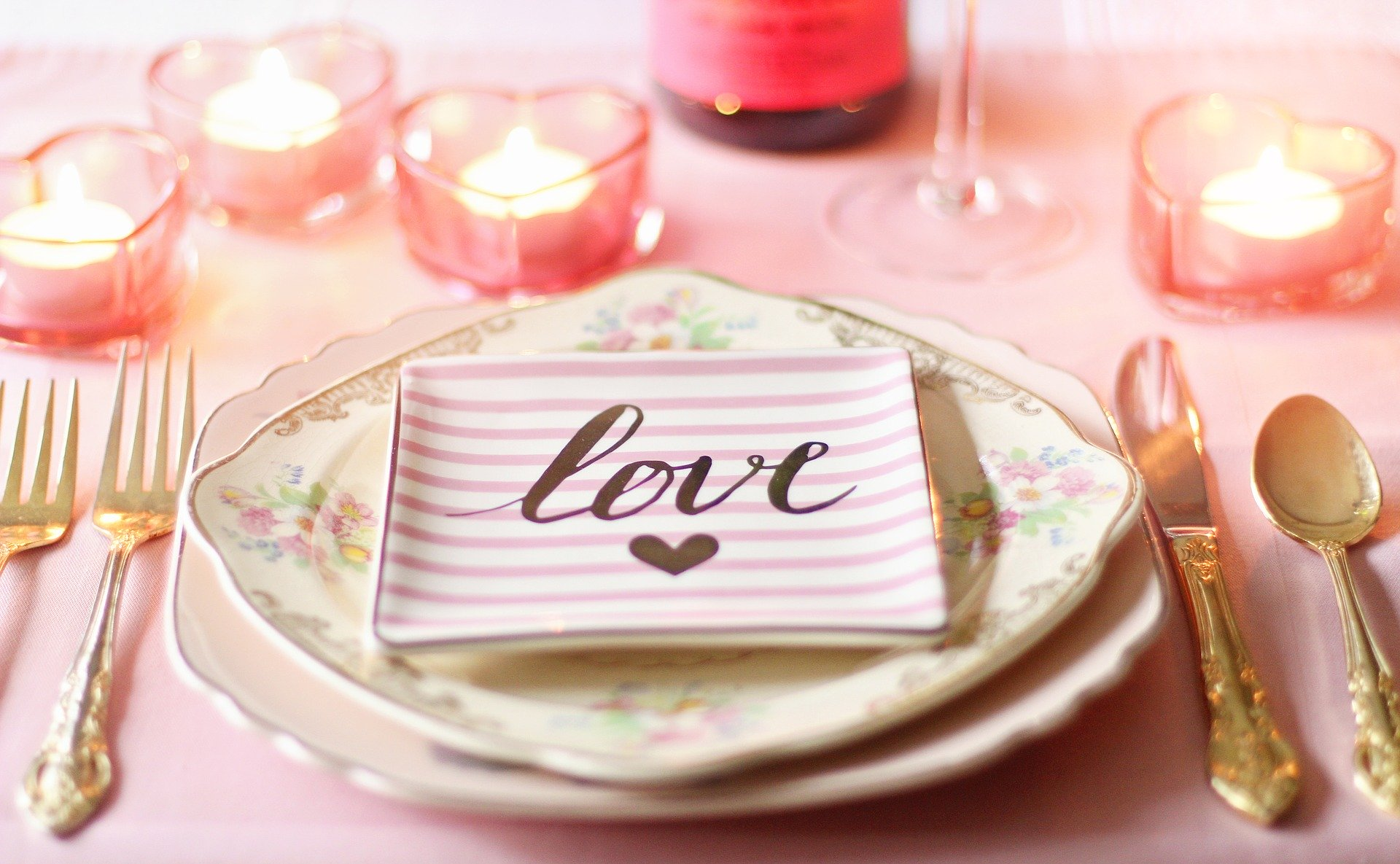 """A table setting for Valentine's Day with gold crockery and floral plates. There is a pink and white plate with """"Love"""" written on it with a heart."""
