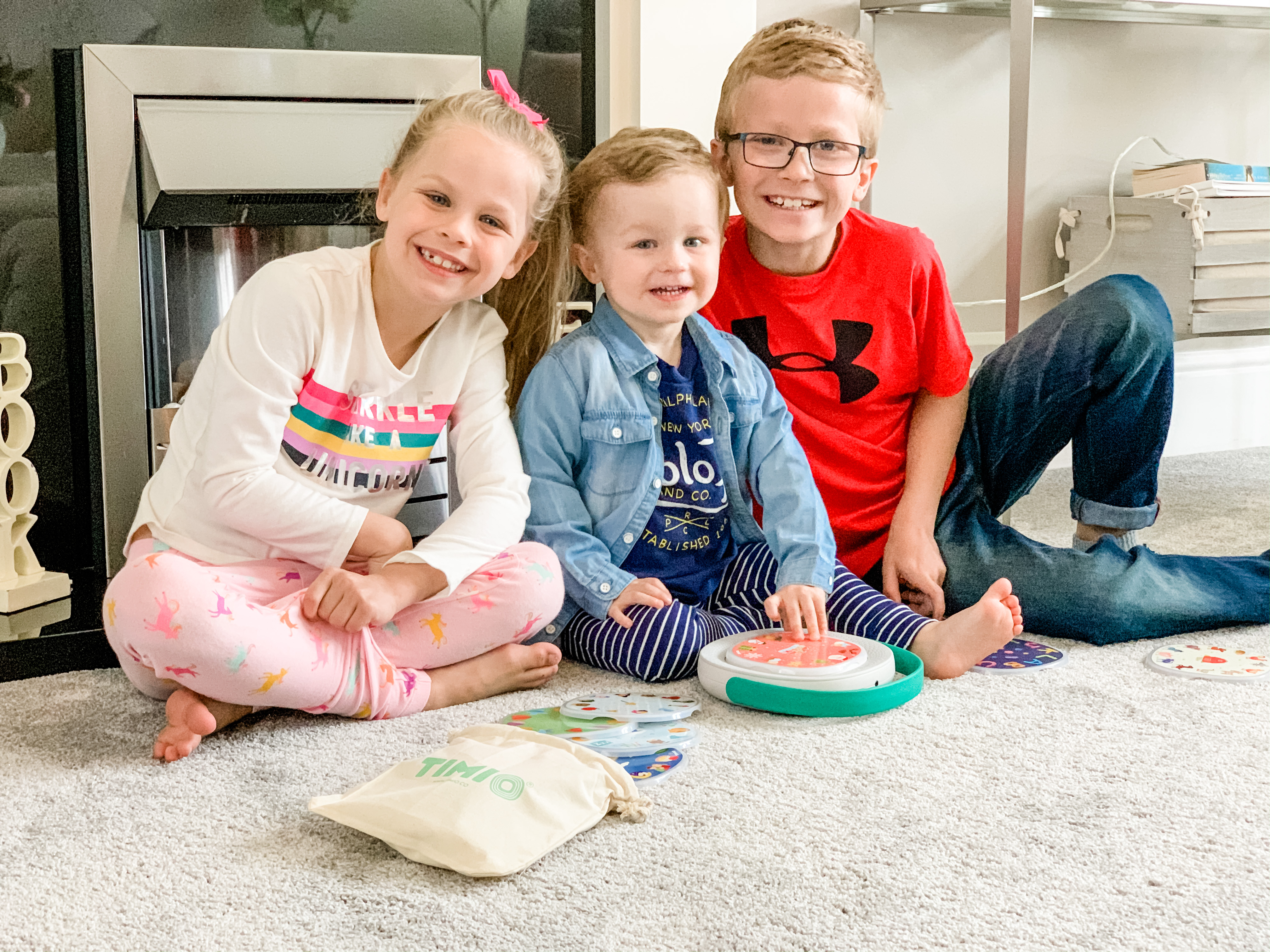 3 children smiling for the camera while playing with a TIMIO kid's audio and music player for learning