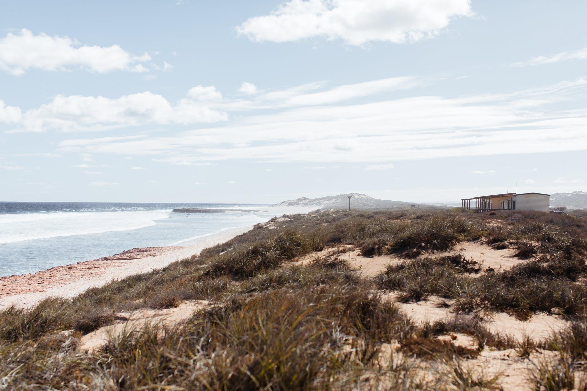mountainous beach with houses against foamy sea