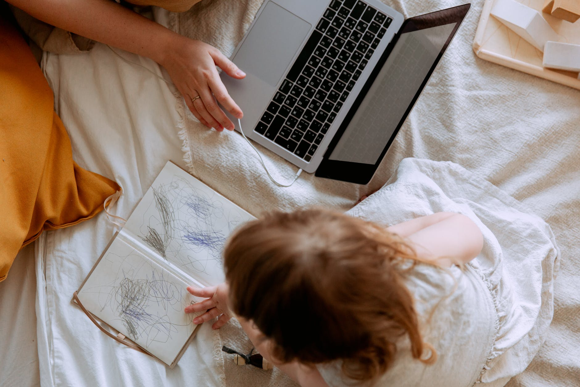 crop mother and daughter using laptop and drawing