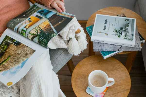 Home interior hacks for renters unrecognizable woman reading magazine in armchair near table with mug
