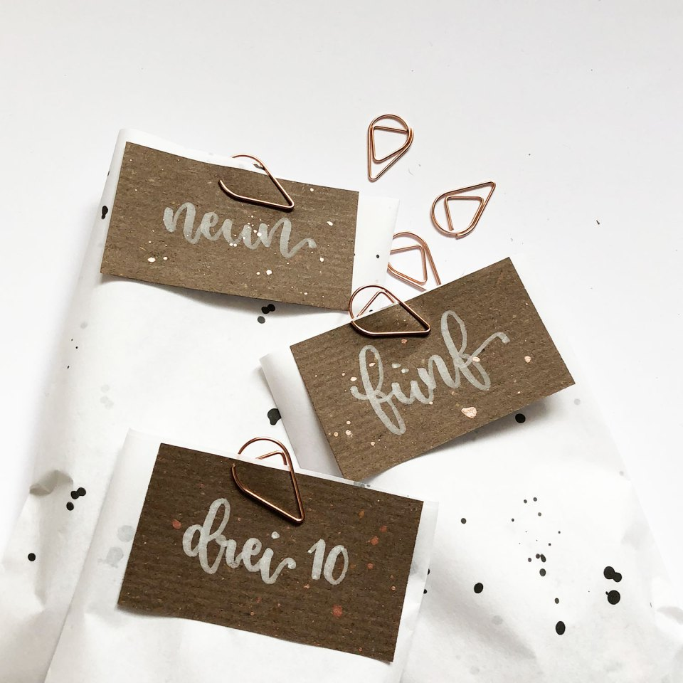 Adventskalender Zahlen DIY weißer Brushpen auf braunem Papier