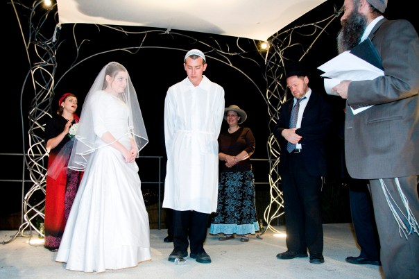 Poised over the glass. At our wedding, we switched things around, according to the Jerusalem custom, and broke the glass before reciting the sheva brachot, so the wedding didn't end with the breaking of the glass.